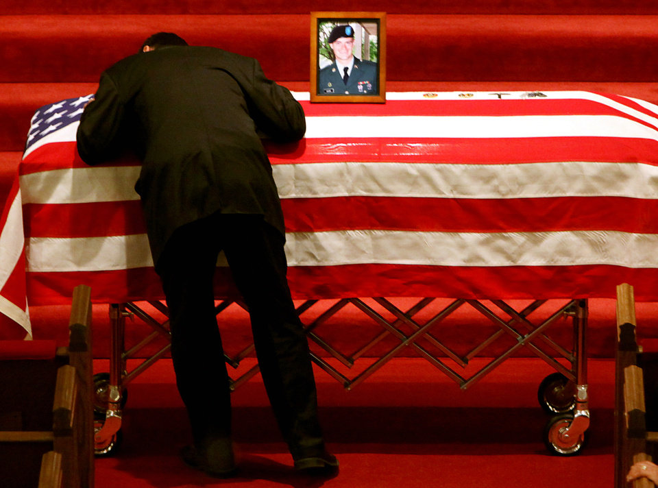 A relative of Gary Moore hugs his casket as services for Gary Moore begin at Southwest Baptist Church in Oklahoma City on Tuesday, March 24, 2009. Moore was killed in Iraq last week. PHOTO BY JOHN CLANTON, THE OKLAHOMAN