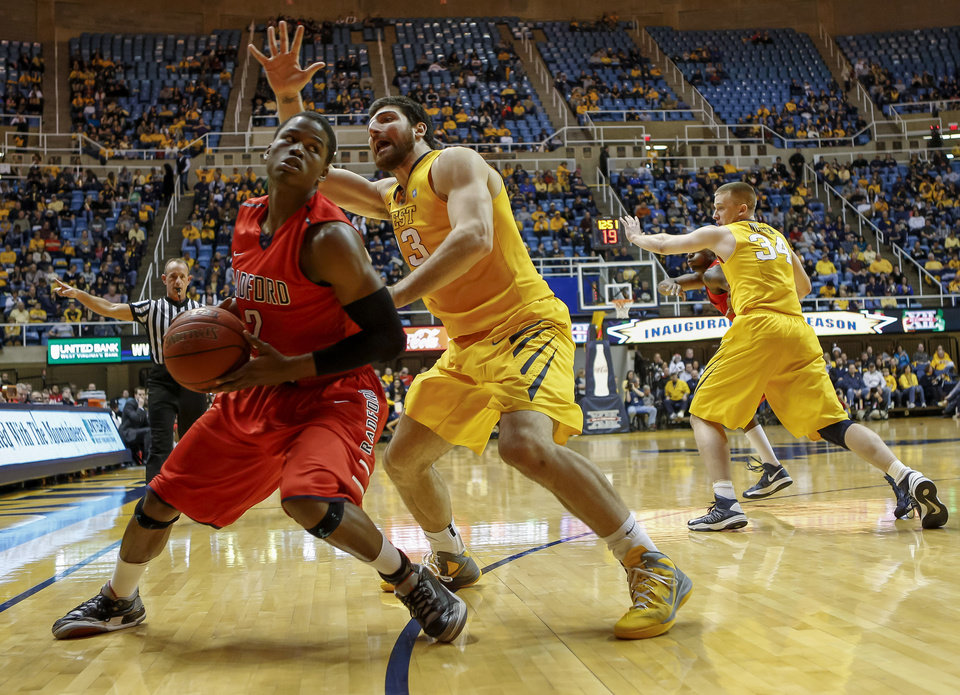 Photo - Radford's Javonte Green (2) is defended by West Virginia's Deniz Kilicli (13) during the first half of an NCAA college basketball game at WVU Coliseum in Morgantown, W.Va., on Saturday, Dec. 22, 2012. (AP Photo/David Smith)