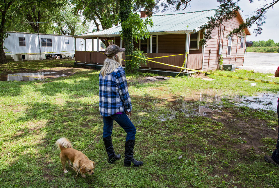 Photo - A Twin Lakes resident watches as her home is threatened by flood waters rushing down the Cimarron River in the Twin Lakes community near Cimarron City, Okla. on Wednesday, May 22, 2019.  [Chris Landsberger/The Oklahoman]