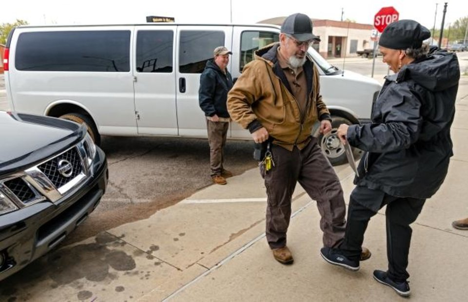 Photo -  Mabel Bassett staff member John Seright and Donna Heins tap feet instead of a handshake after Heins and her staff prepared 200 lunches Clara Belle's for the staff at Mabel Bassett in McLoud, Okla. on Friday, April 3, 2020. Prison volunteers raised money to pay for lunch boxes for staff at the prison.  [Chris Landsberger/The Oklahoman]