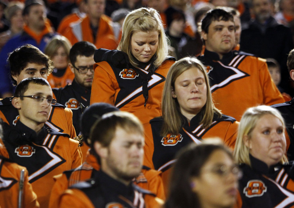 Photo - Members of the OSU Cowboy Marching Band stand during a moment of silence before a college football game between the Oklahoma State University Cowboys (OSU) and the Iowa State University Cyclones (ISU) at Jack Trice Stadium in Ames, Iowa, Friday, Nov. 18, 2011. Oklahoma State University women's basketball coach Kurt Budke, assistant coach Miranda Serna, former state Sen. Olin Branstetter and his wife, Paula, were killed Thursday in a plane crash in Central Arkansas. Photo by Nate Billings, The Oklahoman