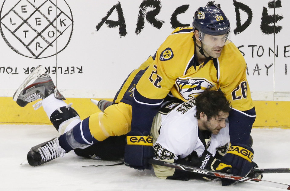 Photo - Pittsburgh Penguins forward Brian Gibbons (49) loses his helmet as he collides with Nashville Predators forward Paul Gaustad (28) in the first period of an NHL hockey game Tuesday, March 4, 2014, in Nashville, Tenn. (AP Photo/Mark Humphrey)