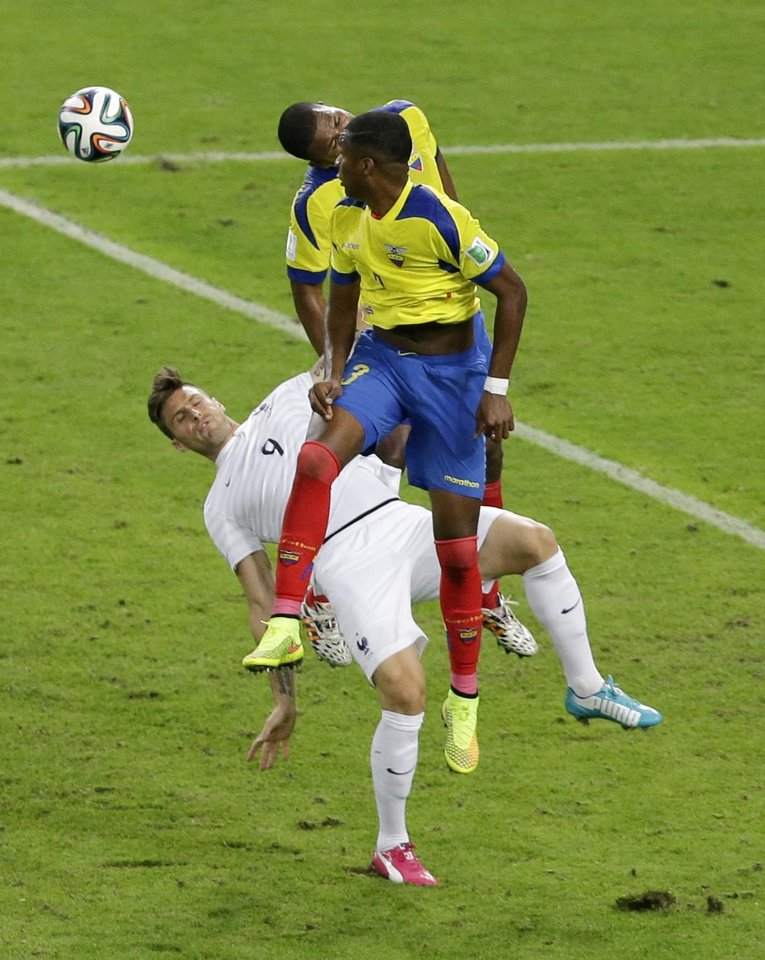 Photo - Ecuador's Frickson Erazo, center, and Jorge Guagua, right, both attempt to head the ball over France's Olivier Giroud during the group E World Cup soccer match between Ecuador and France at the Maracana Stadium in Rio de Janeiro, Brazil, Wednesday, June 25, 2014. (AP Photo/Andrew Medichini)