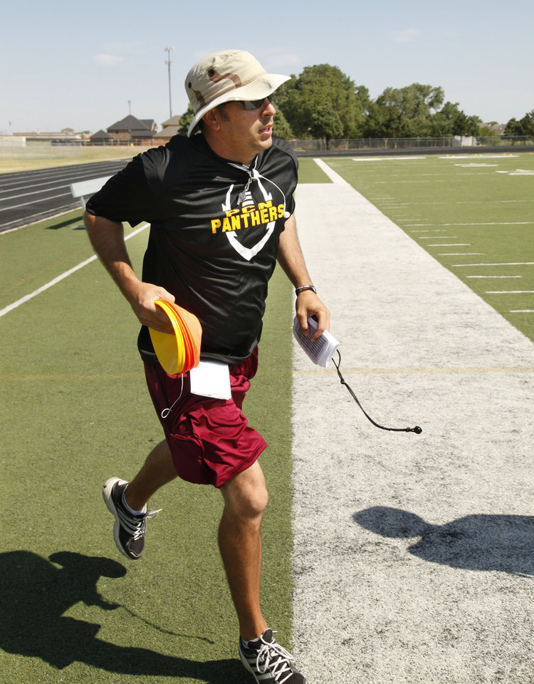 Photo - Head Coach Rod Richardson runs out onto the field during morning practice at Putnam City North High School in Oklahoma City, OK, Monday, August 18, 2014,  Photo by Paul Hellstern, The Oklahoman