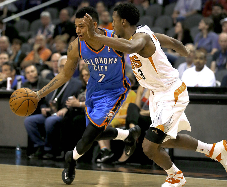 Photo - Phoenix Suns' Ish Smith (3) defends against Oklahoma Thunder guard Diante Garrett  during the first half of an NBA preseason basketball game, Tuesday, Oct. 22, 2013, in Phoenix. (AP Photo/Matt York)