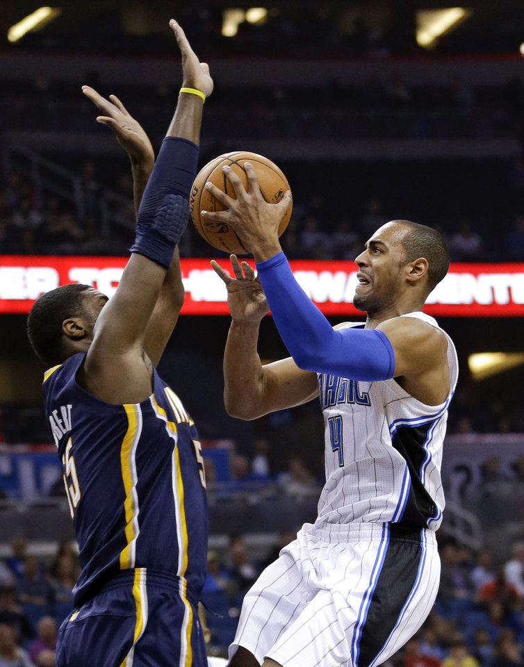 Photo - Orlando Magic's Arron Afflalo (4) takes a shot over Indiana Pacers' Roy Hibbert, left, during the first half of an NBA basketball game in Orlando, Fla., Sunday, Feb. 9, 2014. (AP Photo/John Raoux)