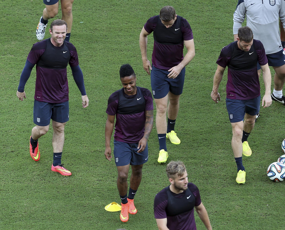 Photo - England players including Wayne Rooney, top left, and Raheem Sterling, second from left, smile during a training session at Arena da Amazonia in Manaus, Brazil, Friday, June 13, 2014.  England plays in group D of the 2014 soccer World Cup. (AP Photo/Martin Mejia)
