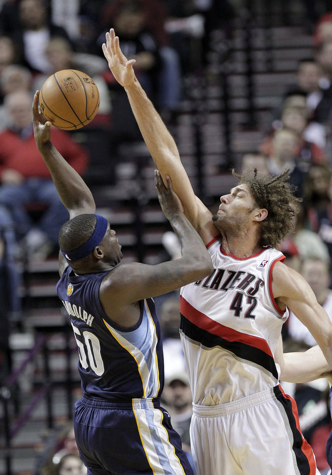 Photo - Memphis Grizzlies forward Zach Randolph, left, shoots over Portland Trail Blazers center Robin Lopez during the second half of an NBA basketball game in Portland, Ore., Tuesday, Jan. 28, 2014.  Randolph led the Grizzlies in scoring with 23 points and pulled in ten rebounds as they beat the Trail Blazers 98-81. (AP Photo/Don Ryan)