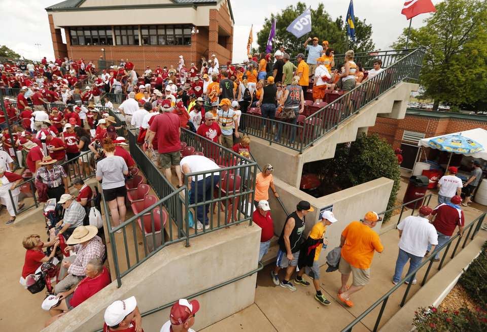 Photo - Fans leave the stands as a lightning delay stops the NCAA super regional at Marita Hynes Field between the University of Oklahoma Sooner (OU) softball team and Tennessee in game two of the  on May 24, 2014 in Norman, Okla. Game one was delayed two hours Friday night.  Photo by Steve Sisney, The Oklahoman