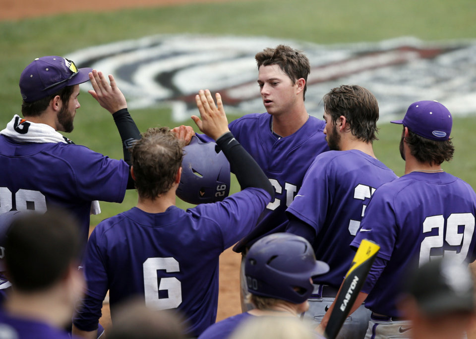 Photo - TCU's Keaton Jones, center, celebrates with teammates after scoring in the eighth inning of a game against Baylor in the Big 12 Conference NCAA college baseball tournament in Oklahoma City, Saturday, May 24, 2014. TCU won 4-1 and advances to the championship game on Sunday. (AP Photo/Sue Ogrocki)