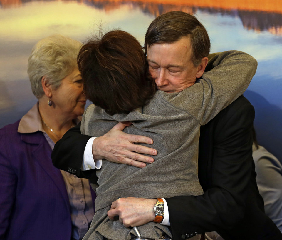 Photo - Colorado Gov. John Hickenlooper, right, is hugged by Rep. Rhonda Fields, D-Aurora, after he signed gun control bills into law at the Capitol in Denver on Wednesday, March 20, 2013. Fields was a co-sponsor of bills on background checks and the size of ammunition magazines. (AP Photo/Ed Andrieski, Pool)