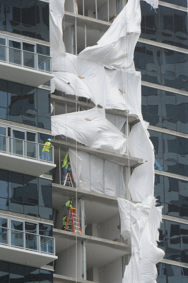 Photo - Mid-morning storm damage from Hurricane Iselle.  Waihonua, an Ala Moana condo under construction has it's plastic covers blown apart by winds Friday Aug. 8, 2014.    (AP Photo/The Star-Advertiser, Craig T. Kojima)