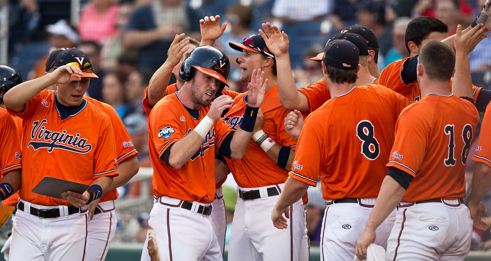 Photo - Virginia's Branden Cogswell (7), center, celebrates with teammates after scoring on a throwing error against TCU in the bottom of the first inning of game 8 during the College World Series at TD Ameritrade Park in Omaha, Neb., Tuesday, June 17, 2014.(AP Photo/The Omaha World-Herald, Mark Davis)