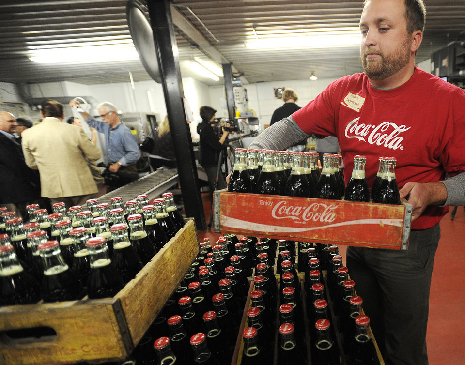 Photo -   FILE - Adam Peterson stakes crates of the last run of 6.5-ounce returnable glass bottles Tuesday, Oct. 9, 2012, at the Coca-Cola Bottling Company in Winona, Minn. The small Coke bottler in Minnesota says it's stopping production of the bottles, which customers could return to get back a 20-cent deposit. The company in Winona, Minn., had been refilling the returnable bottles since 1932 but said it no longer makes business sense to continue doing so. (AP Photo/Winona Daily News, Andrew Link)