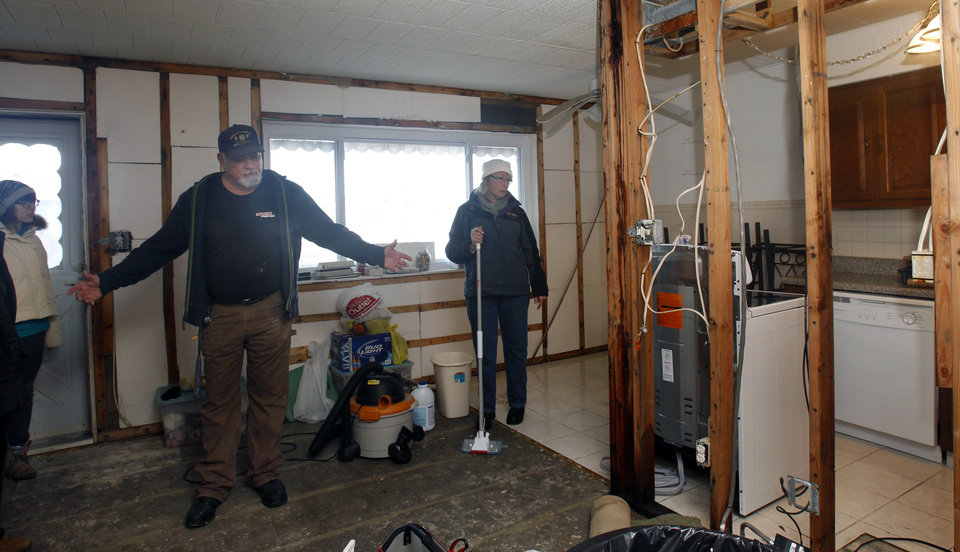 Frank Baker gestures as he and wife, Kim Baker, right, stand in rooms that have the walls stripped out while working to clean up their Superstorm Sandy  damaged home in Seaside Heights, N.J., Thursday, Jan. 3, 2013.   Under intense pressure from angry Republicans, House Speaker John Boehner has agreed to a vote this week on aid for Superstorm Sandy recovery.  (AP Photo/Mel Evans)