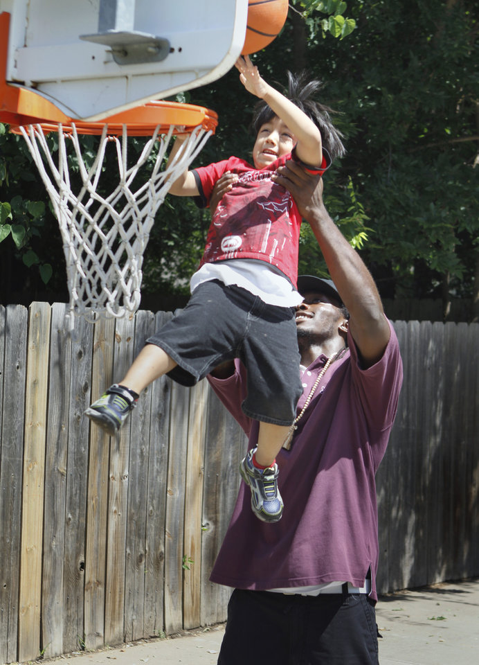 University of Oklahoma (OU) defensive back Quinton Carter lifts Kamuy Padilla for a dunk shot at Kinder Care on Wednesday, June 30, 2010, in Norman Okla. Carter is giving back -- in a big way. Even though he\'s still in college, he has already started a charitable foundation and is heavily involved in projects in Norman and in his hometown of Las Vegas. Photo by Steve Sisney, The Oklahoman