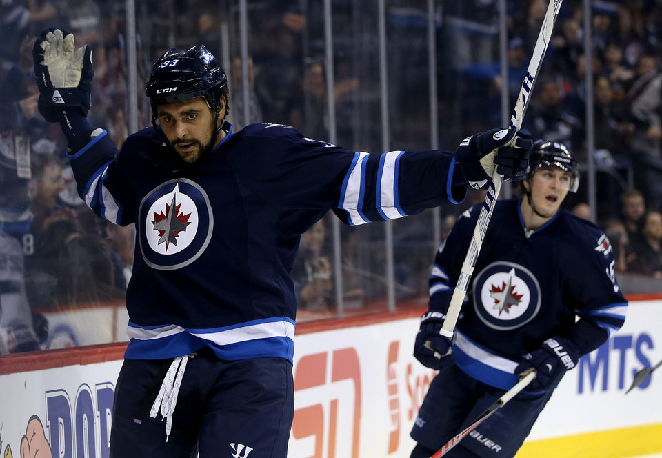 Photo - Winnipeg Jets' Dustin Byfuglien, left, celebrates a power-play goal against the Tampa Bay Lightning during the second period of an NHL hockey game Tuesday, Jan. 7, 2014, in Winnipeg, Manitoba. (AP Photo/The Canadian Press, Trevor Hagan)
