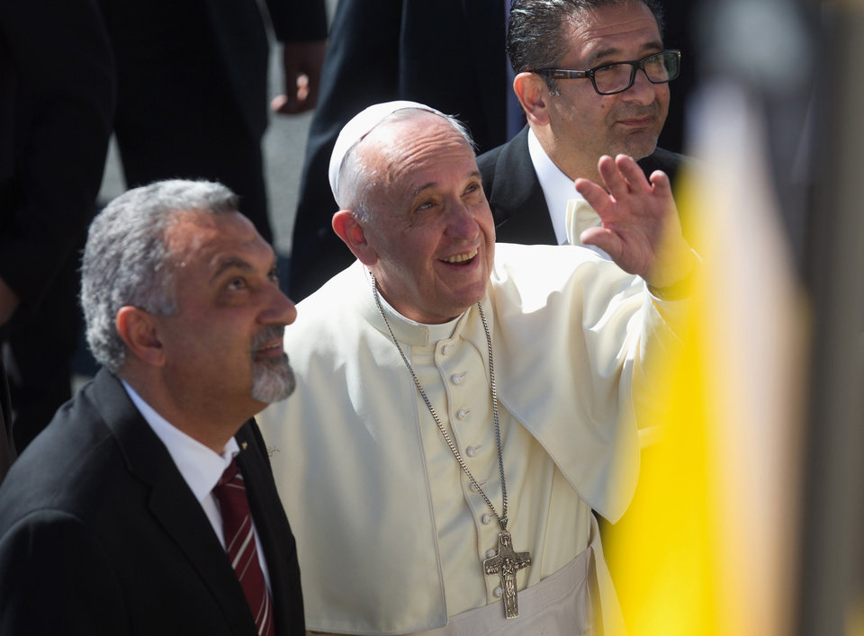 Photo - Pope Francis waves as he arrives in the West Bank town of Bethlehem on Sunday, May 25, 2014. Francis landed Sunday in the West Bank town of Bethlehem in a symbolic nod to Palestinian aspirations for their own state as he began a busy second day of his Mideast pilgrimage. (AP Photo/Menahem Kahana, Pool)