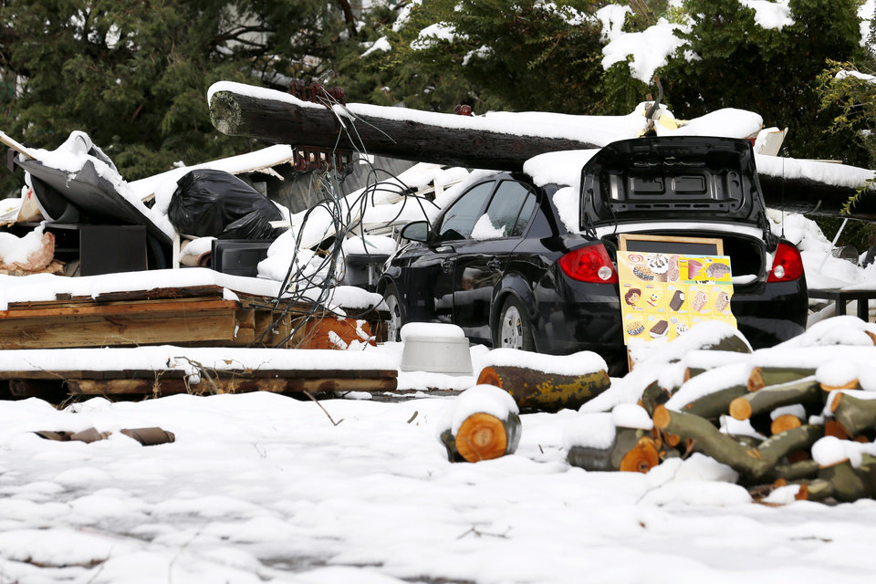 Photo - A down power poll rests on top of a vehicle as snow covered debris from Superstorm Sandy lay in the middle of a street following a nor'easter storm, Thursday, Nov. 8, 2012, in Point Pleasant, N.J.  The New York-New Jersey region woke up to wet snow and more power outages Thursday after the nor'easter pushed back efforts to recover from Superstorm Sandy, that left millions powerless and dozens dead last week. (AP Photo/Julio Cortez) ORG XMIT: NJJC115
