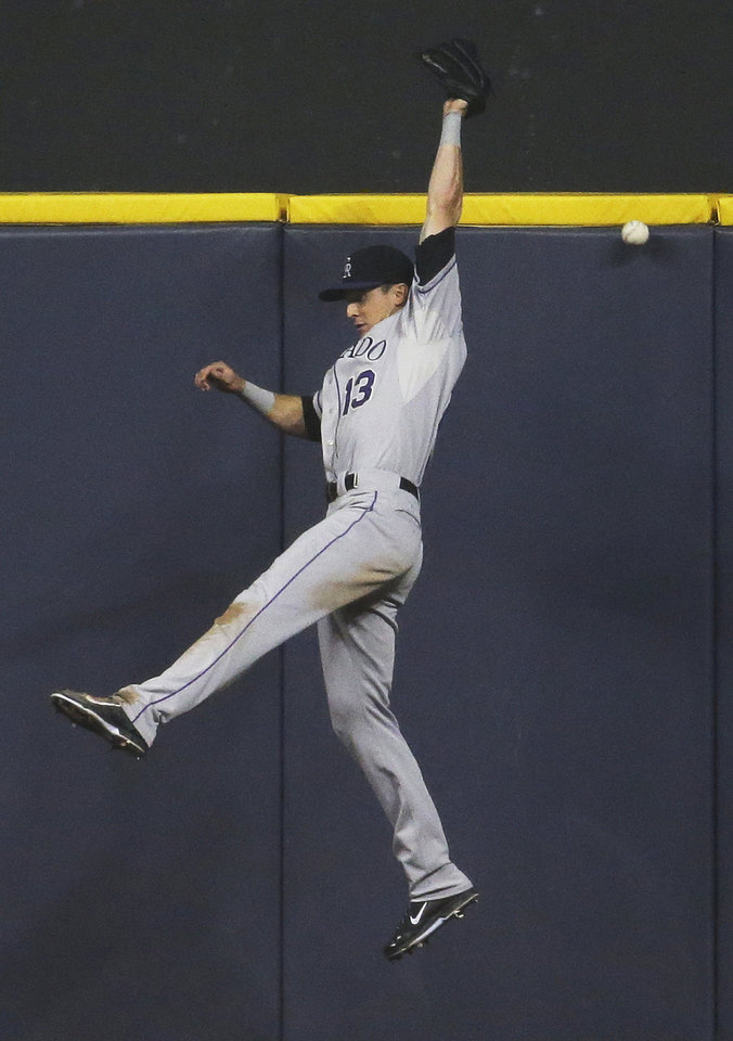 Photo - Colorado Rockies center fielder Drew Stubbs can't catch a single by Milwaukee Brewers' Jonathan Lucroy during the fifth inning of a baseball game Thursday, June 26, 2014, in Milwaukee. (AP Photo/Morry Gash)