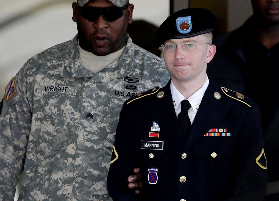 FILE - In this June 25, 2012 file photo, Army Pfc. Bradley Manning, right, is escorted out of a courthouse in Fort Meade, Md. Lawyers for Julian Assange argue before the U.S. military's highest court for public access to legal documents in the court-martial of Pfc. Bradley Manning, the soldier charged with aiding the enemy for allegedly giving hundreds of thousands of classified U.S. documents to Assange's secret-busting website WikiLeaks. (AP Photo/Patrick Semansky, File)