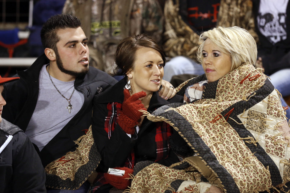 Photo - Meeker supporters Adam and Cylie Holik bundle up with Cylie's mother Bridgette Coleman for the game as the Millwood Falcons play the Meeker Bulldogs in state high school football playoffs on Friday, Nov. 29, 2013, in Meeker, Okla.  Photo by Steve Sisney, The Oklahoman