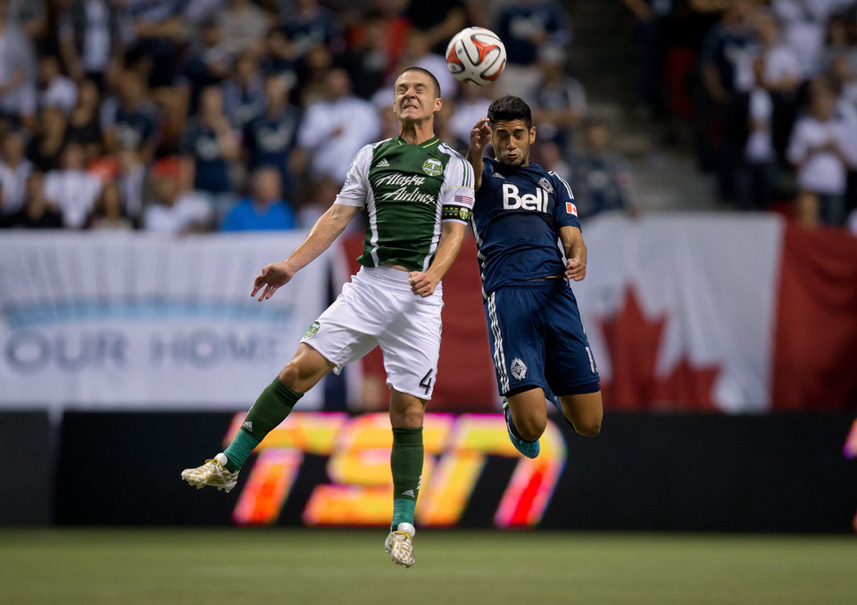 Photo - Portland Timbers' Will Johnson, left, and Vancouver Whitecaps' Matias Laba, of Argentina, vie for the ball during the first half of an MLS soccer game in Vancouver, British Columbia, on Saturday, Aug. 30, 2014. (AP Photo/The Canadian Press, Darryl Dyck)