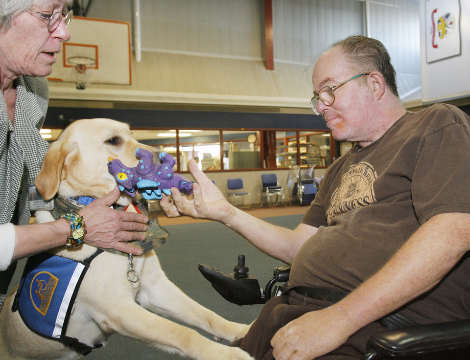 Photo - Vietnam Marine veteran Dale Bruyere works with Ascot, a therapy dog, with creative arts therapist Dawn Truby at the VA Medical Center, Thursday, February 19, 2009. By David McDaniel, The Oklahoman. ORG XMIT: KOD