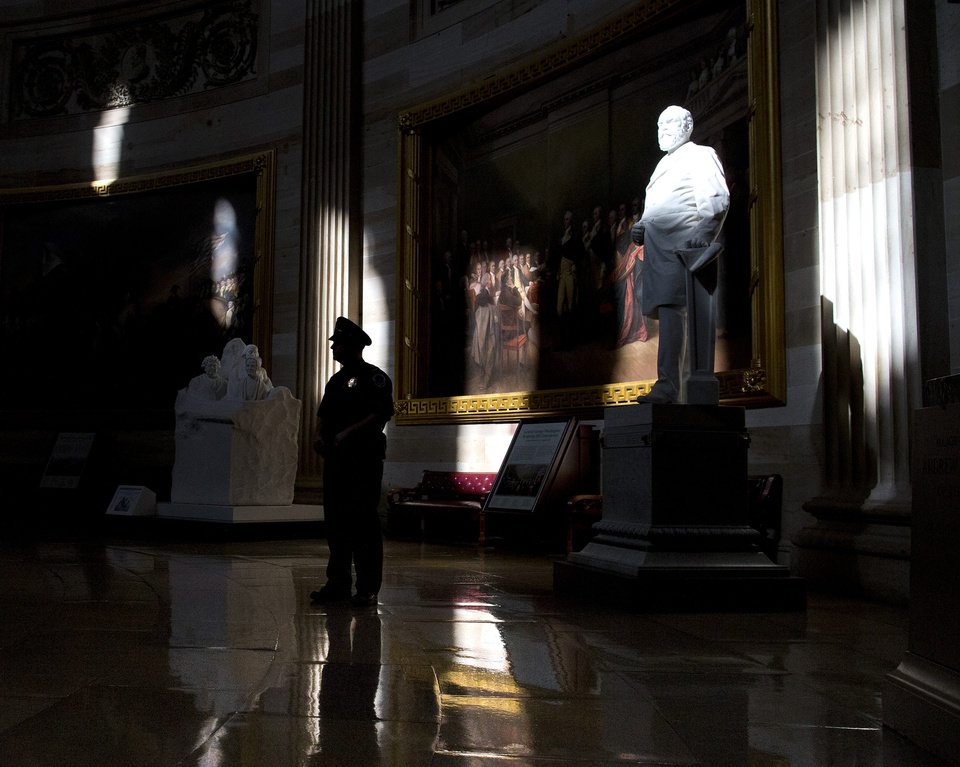 Photo - A Capitol Hill police officer stands in the Capitol Rotunda of the U.S. Capitol building on Monday, Oct. 14, 2013 in Washington. The federal government remains partially shut down and faces a first-ever default between Oct. 17 and the end of the month. The statue at the right is James Garfield, who served as the 20th President of the United States.  (AP Photo/ Evan Vucci)