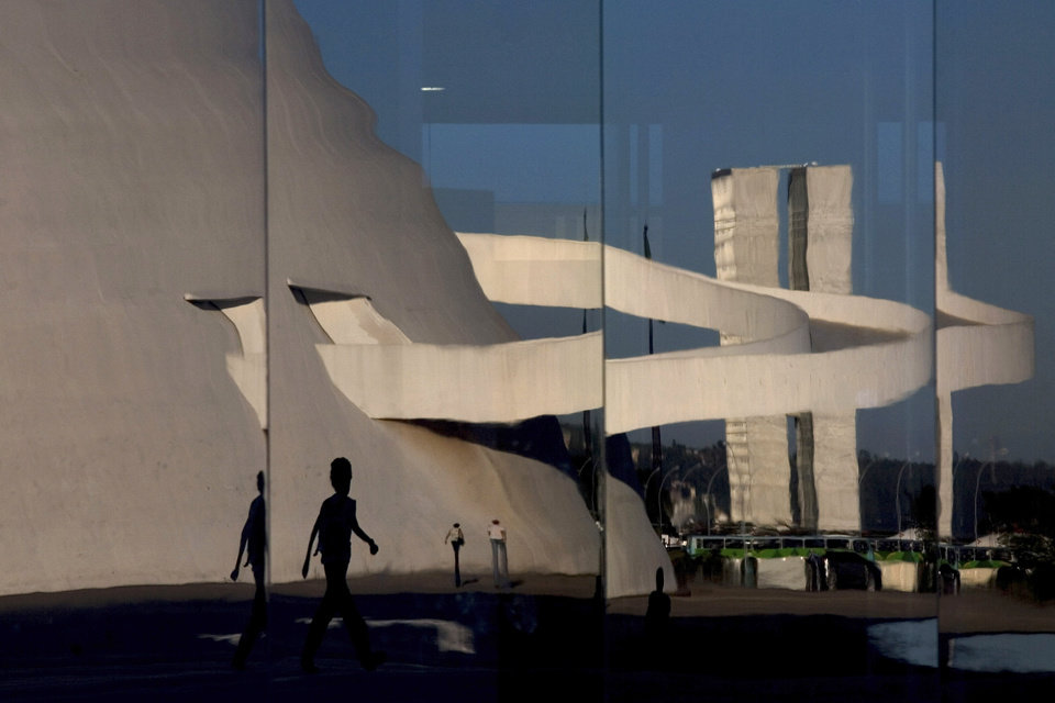 Photo - FILE - In this April 7, 2010 file photo, the National Museum and National Congress are reflected on the glass wall of the National Library, all designed by architect Oscar Niemeyer, in Brasilia, Brazil. According to a hospital spokeswoman on Wednesday, Dec. 5, 2012, famed Brazilian architect Oscar Niemeyer has died at age 104.  (AP Photo/Eraldo Peres, File)