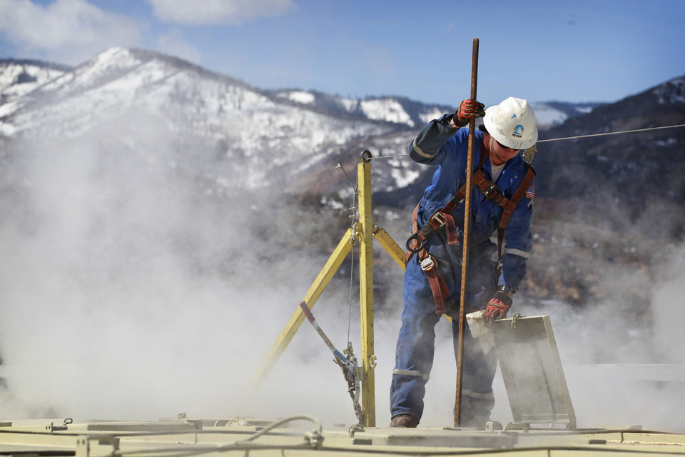 Photo - A worker examines a dipstick to check water levels and temperatures in a series of tanks at an Encana Oil & Gas (USA) Inc. hydraulic fracturing operation at a gas drilling site outside Rifle, Colorado. AP Photo  Brennan Linsley