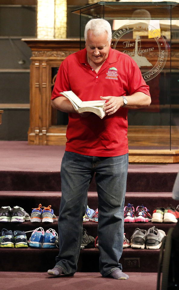 Photo - Pastor Mark McAdow blesses shoes during the Blessing of the Shoes service at First Church in downtown Oklahoma City Saturday, April 23, 2016. The service blessed the shoes of those running in the Memorial Marathon Sunday morning. Photo by Sarah Phipps, The Oklahoman