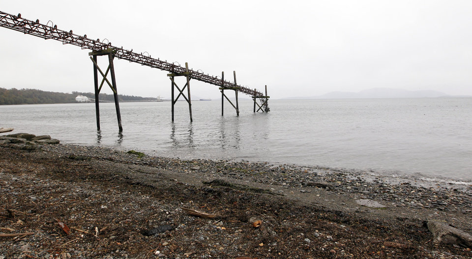 Photo -   In this photo taken Oct. 23, 2012, a dilapidated structure is seen jutting out into the Strait of Georgia along the beach just south of the location of a proposed coal exporting terminal in Ferndale, Wash., just north of Bellingham, Wash. In the distance behind are an existing aluminum plant and oil refinery. The progressive college town of Bellingham is at the center of one of the fiercest environmental debates in the region: should the Northwest become a hub for exporting U.S. coal to Asia? A proposal to build one of as many as five coal terminals here has divided the town, pitting union and businesses that welcome jobs against environmentalists who worry about coal dust and greenhouse gas emissions. A trade group is running TV ads touting the projects, while numerous cities such as Seattle and Portland are opposing coal trains through their communities. (AP Photo/Elaine Thompson)