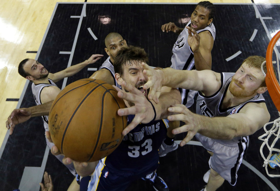 Photo - Memphis Grizzlies' Marc Gasol, center, is defended by, from left to right, San Antonio Spurs' Manu Ginobili, Tim Duncan, Kawhi Leonard and Matt Bonner during the first half in Game 1 of a Western Conference Finals NBA basketball playoff series on Sunday, May 19, 2013, in San Antonio. (AP Photo/Eric Gay)
