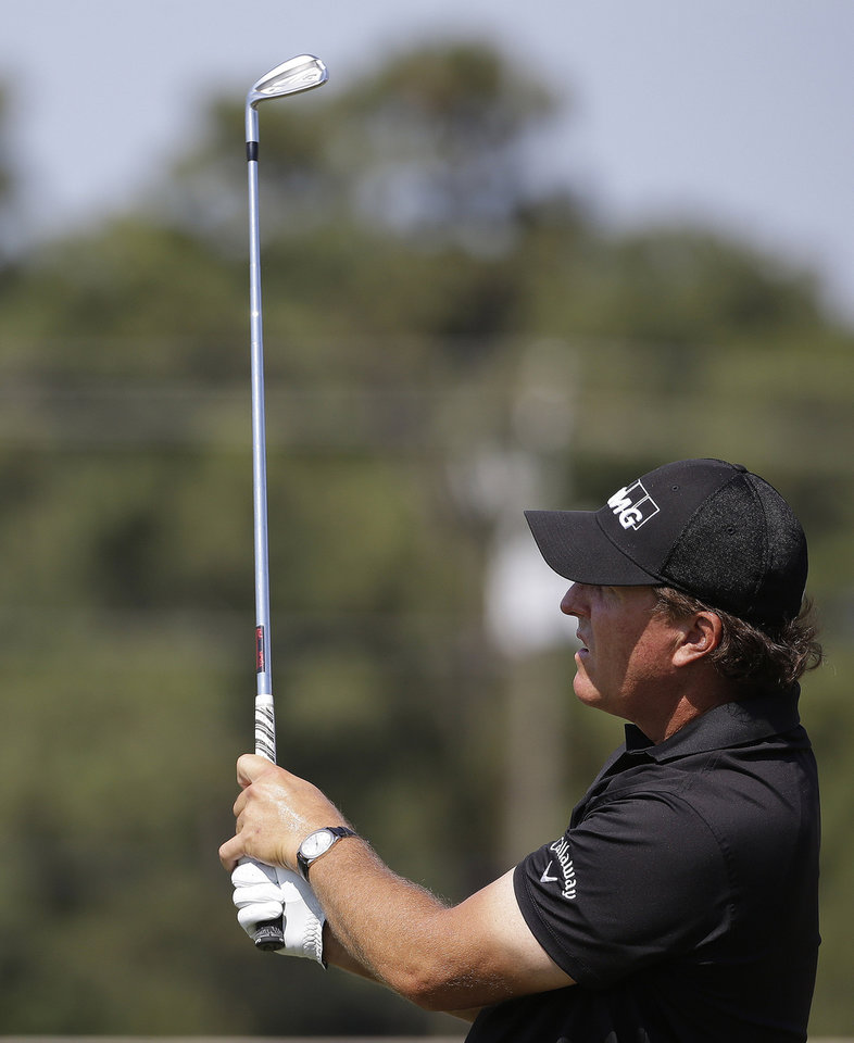 Photo - Phil Mickelson views his shot on the driving range before a practice round for the U.S. Open golf tournament in Pinehurst, N.C., Wednesday, June 11, 2014. The tournament starts Thursday. (AP Photo/David Goldman)
