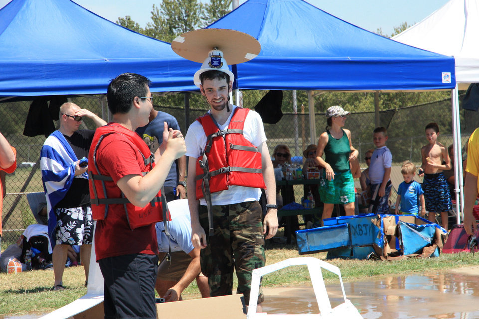 "ThunderCats members Sanford Ang, left, and Matthew Maupin talk before launching their cardboard boat Saturday at the 11th Annual Tinker Cardboard Boat Regatta. Maupin is wearing the radar dome for their ""AWACS in a Box"" entry. Photo by Thomas Maupin"