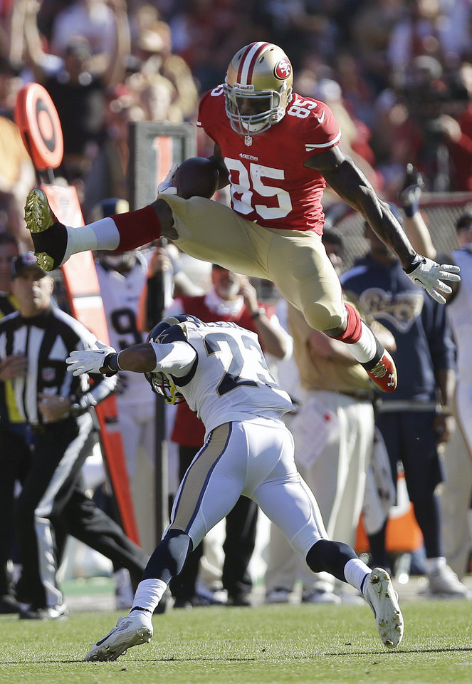 Photo -   San Francisco 49ers tight end Vernon Davis jumps over St. Louis Rams free safety Rodney McLeod on Dec. 1 during the an NFL football game in San  Francisco.  AP File Photo   Marcio Jose Sanchez -