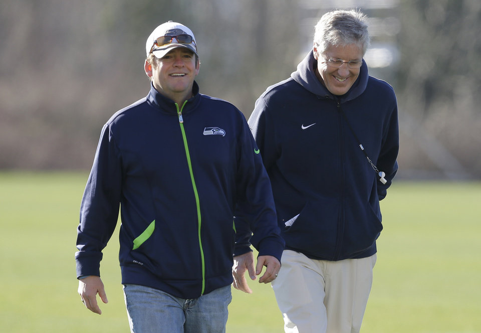 Photo - Seattle Seahawks general manager John Schneider, left, walks with head coach Pete Carroll, right, after NFL football practice, Friday, Jan. 24, 2014, in Renton, Wash. The Seahawks will play the Denver Broncos Feb. 2, 2014 in the Super Bowl. (AP Photo/Ted S. Warren)