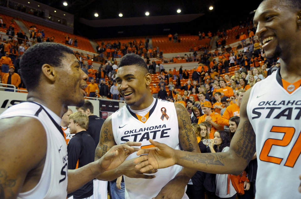 Oklahoma State guard Marcus Smart, left, celebrates with guard Le\'Bryan Nash, center, and forward Kamari Murphy, right following an NCAA college basketball game against Baylor in Stillwater, Okla., Wednesday, Feb. 6, 2013. Oklahoma State won 69-67. (AP Photo/Brody Schmidt)