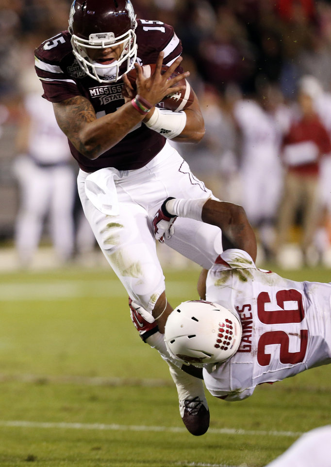 Photo - Mississippi State quarterback Dak Prescott (15) is tackled by Arkansas safety Rohan Gaines (26) after a short run in the first half of an NCAA college football game in Starkville, Miss., Saturday, Nov. 1, 2014. (AP Photo/Rogelio V. Solis)