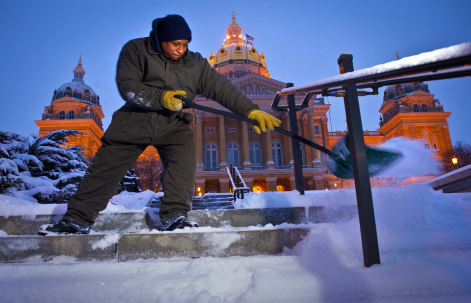 Photo - Billie Byrd of Des Moines clears the steps of the Iowa Capitol Friday Feb. 22, 2013, after an overnight snowstorm dumped six inches in Des Moines.  The snowstorm left behind varying amounts of snow and ice across the Midwest, causing difficult travel conditions. Powerful wind gusts created large snow drifts on many roadways, making navigating the slick conditions a challenge.   (AP Photo/The Des Moines Register, Rodney White)