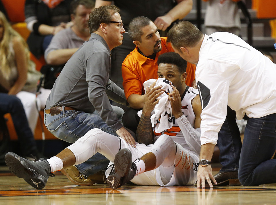 Photo - OSU's Jeff Newberry (22) sits on the court after being hurt in the second half during a men's college basketball game between Oklahoma State and Missouri State at Gallagher-Iba Arena in Stillwater, Okla., Saturday, Dec. 5, 2015. Missouri State won 64-63. Photo by Nate Billings, The Oklahoman