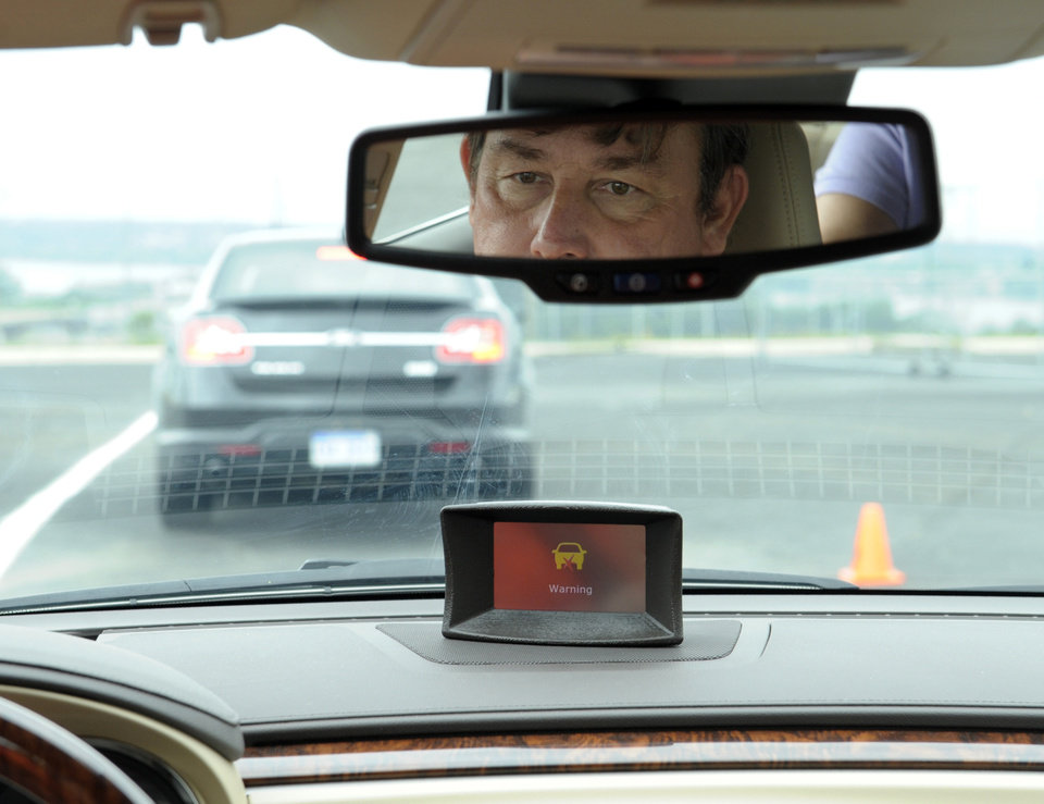 Photo -   In this photo taken, Tuesday, May 22, 2012, professional test driver Dave McMillan, from Los Angeles, demonstrates the dashboard warning signal in a Buick Lacrosse at an automobile test area in Oxon Hill. The display at a recent transportation conference was a peek into the future of automotive safety: cars that to talk to each other and warn drivers of impending collisions. Later this summer, the government is launching a yearlong, real-world test involving nearly 3,000 cars, trucks and buses using volunteer drivers in Ann Arbor, Mich. (AP Photo/Susan Walsh)