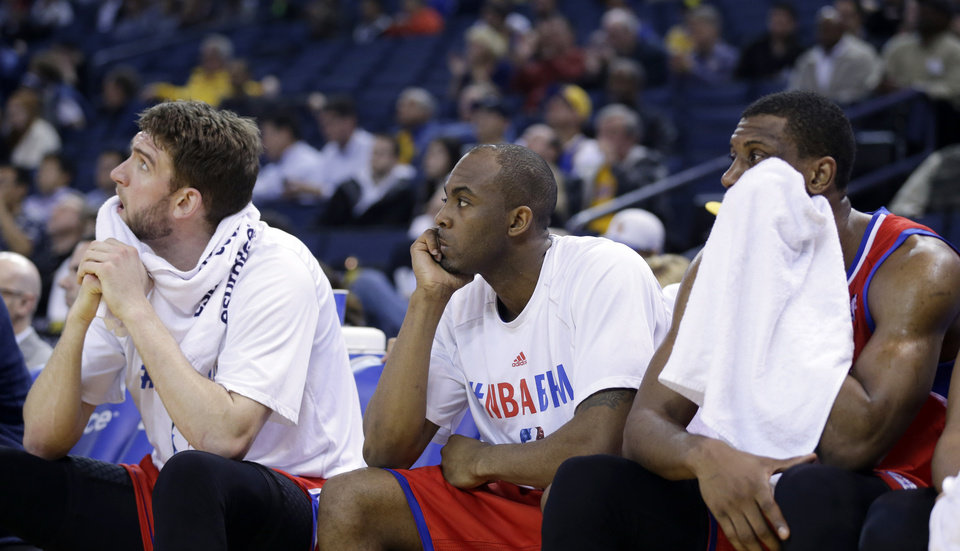 Photo - Philadelphia 76ers players watch from the bench in the closing seconds of a 123-80 loss to the Golden State Warriors during the second half of an NBA basketball game on Monday, Feb. 10, 2014, in Oakland, Calif. (AP Photo/Marcio Jose Sanchez)
