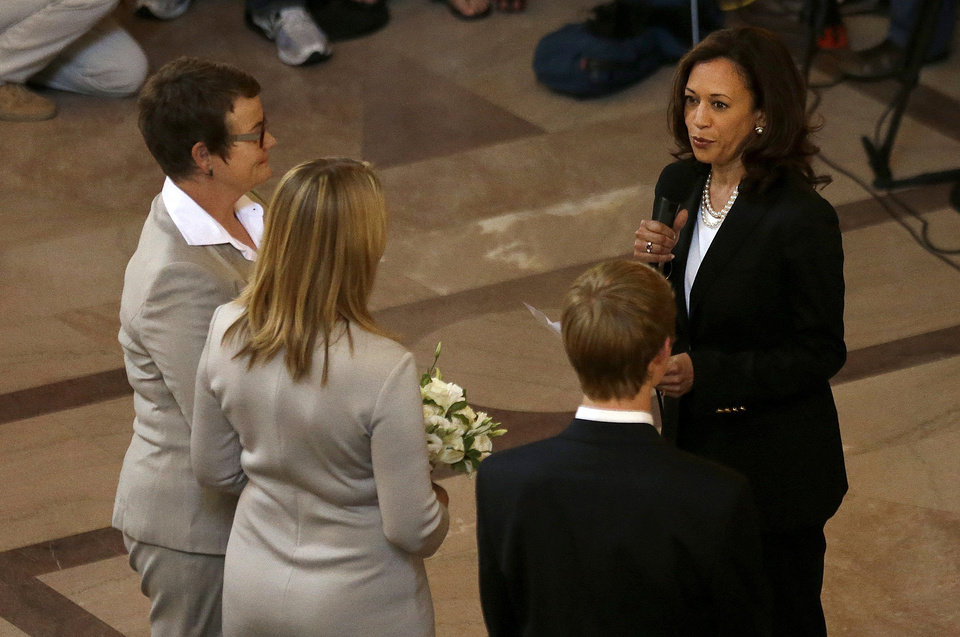 Photo - Attorney General Kamala Harris, right, officiates the wedding of Kris Perry, left, and  Sandy Stier, second from left, in San Francisco, Friday, June 28, 2013. Stier and Perry were married Friday, June 28, 2013, after a federal appeals court on Friday cleared the way for the state of California to immediately resume issuing marriage licenses to same-sex couples after a 4 1/2-year freeze. (AP Photo/Jeff Chiu)