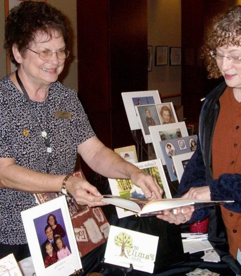 Genealogist Nona Thompson shows Robin Roads some of the holiday gifts possible from using genealogy information. Thompson will be showing Edmond Genealogical Society members how to make gifts at a program on Dec. 17. PHOTO PROVIDED
