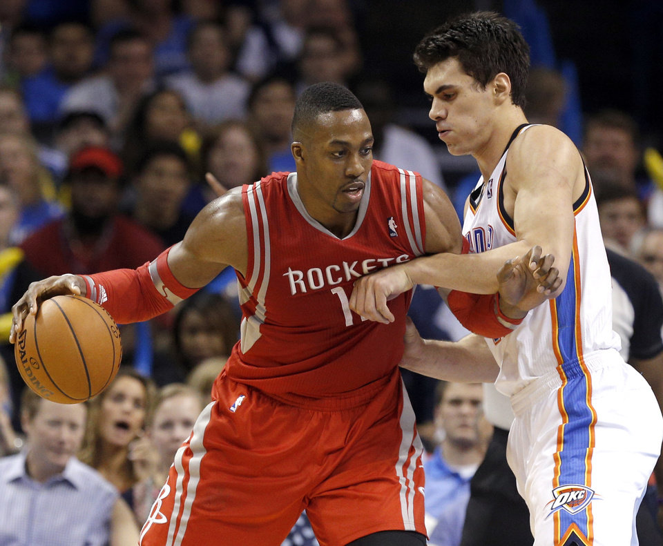 Photo - Oklahoma City's Steven Adams (12) defends against Houston's Dwight Howard (12) during the NBA game between the Oklahoma City Thunder and Houston Rockets at the  Chesapeake Energy Arena  in Oklahoma City, Okla., Tuesday, March 11, 2014. Photo by Sarah Phipps, The Oklahoman