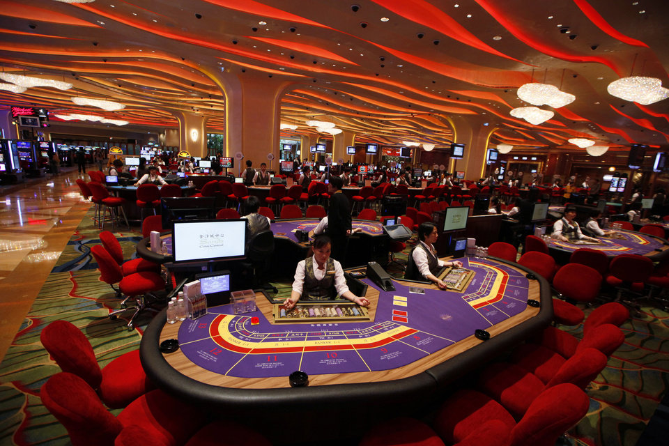 Photo - In this Sept. 20, 2012 photo, Croupiers sit at a baccarat gaming table inside a casino during the opening day of Sheraton Macao Hotel at the Sands Cotai Central in Macau. Macau is in the midst of one of the greatest gambling booms the world has ever known. To rival it, Las Vegas would have to attract six times as many visitors  essentially every man, woman and child in America. Wynn Las Vegas now makes nearly three-quarters of its profits in Macau. Sands, which owns the Venetian and Palazzo, earns two-thirds of its revenue there. (AP Photo/Kin Cheung)