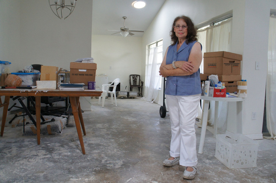 Linda Lipofsky, of Orlando, stands in the home that hurricanes destroyed in 2004. After eight grueling years, during which time a contractor ran off with the insurance money before finishing the job, she is moving back in thanks to the heroic efforts of Rebuilding Together. Photo courtesy of Rebuilding Together.  <strong></strong>