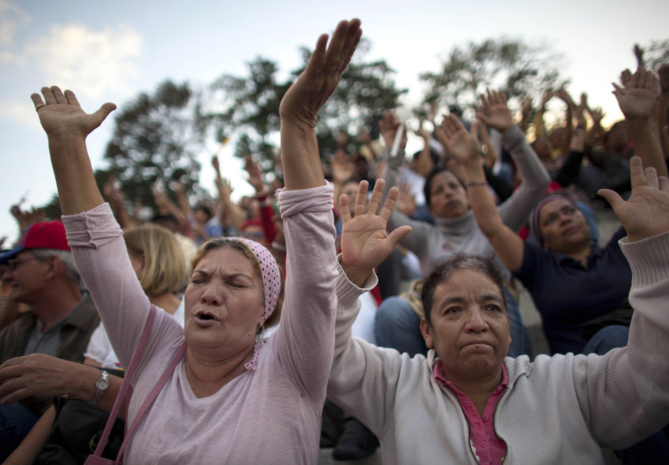 People pray for Venezuela's President Hugo Chavez as he remains in a hospital undergoing cancer treatment during a vigil in Caracas, Venezuela, Friday, Feb. 22, 2013. Chavez hasn't been seen since he returned to Venezuela on Monday from Cuba, where for 10 weeks he was recovering and fighting complications following his latest cancer surgery Dec. 11. (AP Photo/Ariana Cubillos)